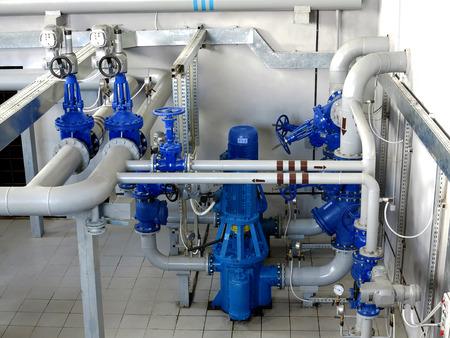 Water pompstation, industrieel interieur en pijpen. Watersysteem kleppen, elektronische motorregeling watervoorziening Stockfoto