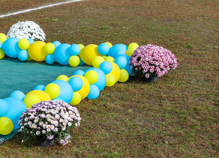 Fragment festive floral decorations and bouquets of flowers sites yellow and blue balloons colors of the national flag of Ukraine
