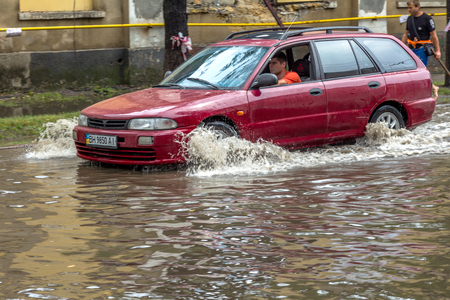 ODESSA, UKRAINE - July 24, 2014: As a result of heavy rainfall disaster flooded streets. Cars fording. Flooding. July 24, 2014 in Odessa, Ukraine  Editorial