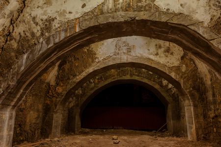An old abandoned tunnel in an underground wine cellar. Entrance to catacombs. Dungeon Old stone fortress. As creative background for staging dark design. Mystical interior of ancient dungeon
