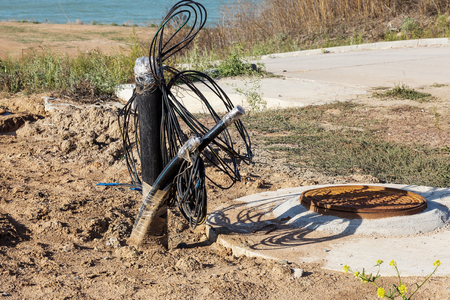 Output of electrical, signal telephone cables and fiber optic cable from earth trench near switching well. Telephone cable and telephone lines. Otic-fiber switching systems
