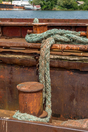 Old rusty iron mooring bollard and the old worn rope tow barges and boats in the Danube river port, Ukraine