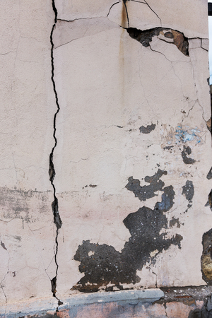 An old destroyed wall with large large cracks.