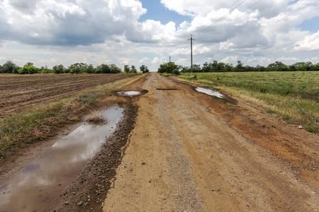 Damaged road, cracked asphalt sword with potholes and spots, Ukraine. Very bad asphalt road with large holes. Terrible technology construction roads. Numerous dangerous failures. Bad road. Road repair