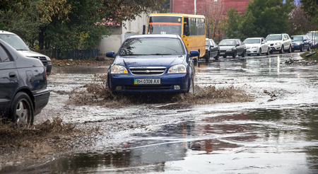 ODESSA, UKRAINE - 21 October 2015: As a result of heavy rains flooded the streets of big puddles. Cars traveling in the rain on a wet road heavily sprayed water and dirt Editorial