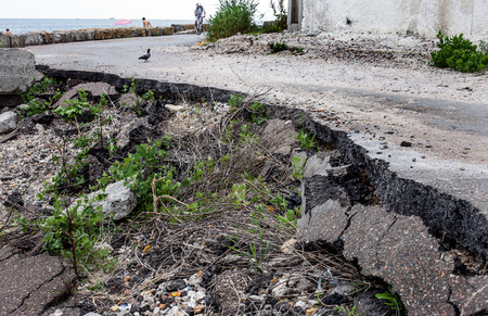 Due to violations of technology in the construction of roads, heavy rain and big waves of the sea washed away the asphalt road and formed numerous dangerous failures 스톡 콘텐츠