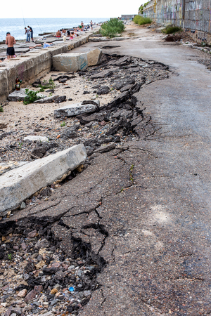 Due to violations of technology in the construction of roads, heavy rain and big waves of the sea washed away the asphalt road and formed numerous dangerous failures Stock Photo