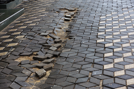 Damaged asphalt road with potholes, caused by freeze-thaw cycles in winter. Bad road. Broken pavements sidewalks on sidewalk. pavement with paving slabs with defects and cracks coming in perspective Banco de Imagens