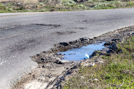 Damaged asphalt road with potholes caused by freezing and thawing cycles during the winter. Poor road.