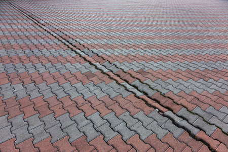 Damaged asphalt road with potholes, caused by freeze-thaw cycles in winter. Bad road. Broken pavements sidewalks on sidewalk. pavement with paving slabs with defects and cracks coming in perspective Stock Photo