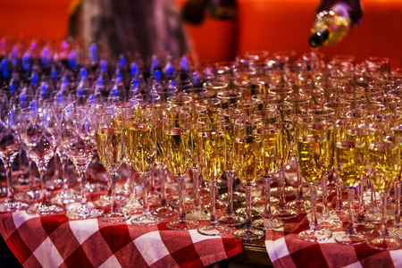Bright abstract background of glass goblets with wine. Unusual bright abstract background of wine strings for decoration of a restaurant. Selective not deep focus, blur