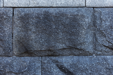 Gray granite texture with a natural pattern for the background or design work. Ragged surface from natural granite background with wild ragged surface of unpolished expensive luxury stone for interior