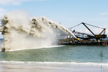 Work dredger dredging with sand washing on beaches. Special dredging hose for sand to create new land. Sand washing on sea beaches. Dredging, washing out sand on beach during construction sea terminal Stock fotó