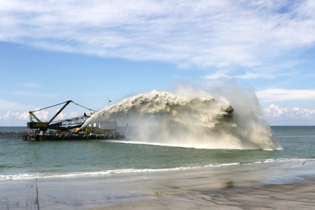 Work dredger dredging with sand washing on beaches. Special dredging hose for sand to create new land. Sand washing on sea beaches. Dredging, washing out sand on beach during construction sea terminal Foto de archivo