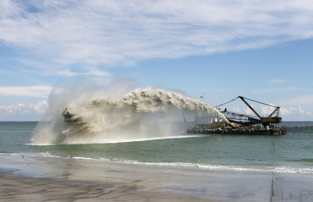 Work dredger dredging with sand washing on beaches. Special dredging hose for sand to create new land. Sand washing on sea beaches. Dredging, washing out sand on beach during construction sea terminal Stock Photo