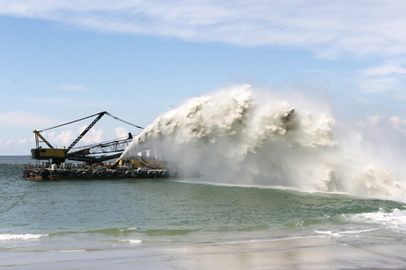 Work dredger dredging with sand washing on beaches. Special dredging hose for sand to create new land. Sand washing on sea beaches. Dredging, washing out sand on beach during construction sea terminal 免版税图像