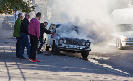 ODESSA, UKRAINE - Oct. 13 2018: Burning car in middle of highway. Sudden Fire from short circuit wiring an old car. Fire in engine compartment began to absorb entire old car is on fire. Road accident