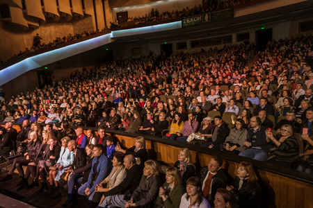 Odessa, Ukraine - November 4, 2018: Large crowd of spectators with pleasure in theater, at concert Celentano tribute during a creative light and musical show. Cheerful bright show in the party club