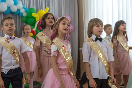 Odessa, Ukraine - May 31,2018: Children's musical group sing and dance on stage during graduation concert of elementary school. Children play. Emotional children's show on stage. Children's creativity Standard-Bild - 127003358