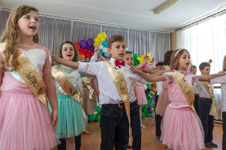 Odessa, Ukraine - May 31,2018: Children's musical group sing and dance on stage during graduation concert of elementary school. Children play. Emotional children's show on stage. Children's creativity Banque d'images - 127003388