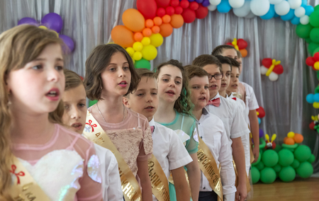 Odessa, Ukraine - May 31,2018: Children's musical group sing and dance on stage during graduation concert of elementary school. Children play. Emotional children's show on stage. Children's creativity Standard-Bild - 127003398