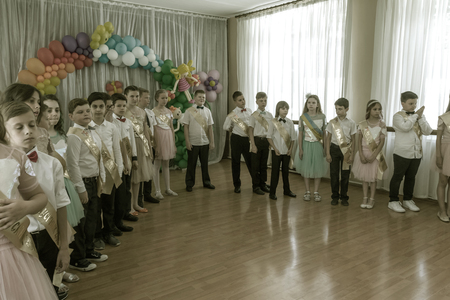 Odessa, Ukraine - May 31,2018: Children's musical group sing and dance on stage during graduation concert of elementary school. Children play. Emotional children's show on stage. Children's creativity Foto de archivo - 127003425