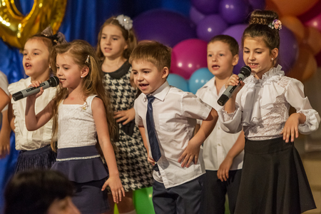 Odessa, Ukraine - May 31,2018: Children's musical group sing and dance on stage during graduation concert of elementary school. Children play. Emotional children's show on stage. Children's creativity Standard-Bild - 127003457