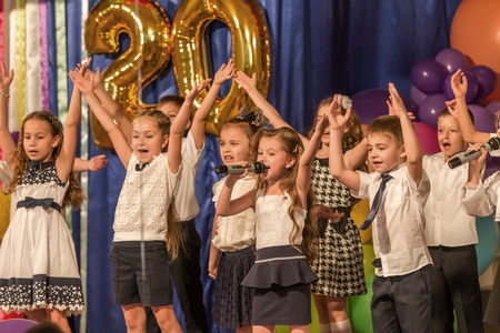 Odessa, Ukraine - May 31,2018: Children's musical group sing and dance on stage during graduation concert of elementary school. Children play. Emotional children's show on stage. Children's creativity Standard-Bild - 127003463