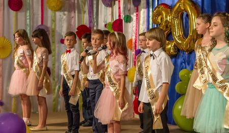 Odessa, Ucrania - 31 de mayo de 2018: el grupo musical infantil canta y baila en el escenario durante el concierto de graduación de la escuela primaria. Los niños juegan. Espectáculo infantil emocional en el escenario. Creatividad infantil