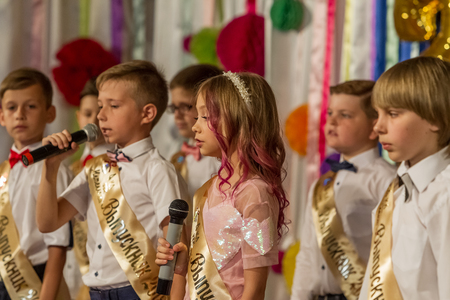 Odessa, Ukraine - May 31,2018: Children's musical group sing and dance on stage during graduation concert of elementary school. Children play. Emotional children's show on stage. Children's creativity Standard-Bild - 127003488