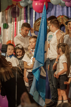Odessa, Ukraine - May 31,2018: Children's musical group sing and dance on stage during graduation concert of elementary school. Children play. Emotional children's show on stage. Children's creativity Standard-Bild - 127003525