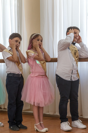 Odessa, Ukraine - May 31,2018: Children's musical group sing and dance on stage during graduation concert of elementary school. Children play. Emotional children's show on stage. Children's creativity Foto de archivo - 127003535