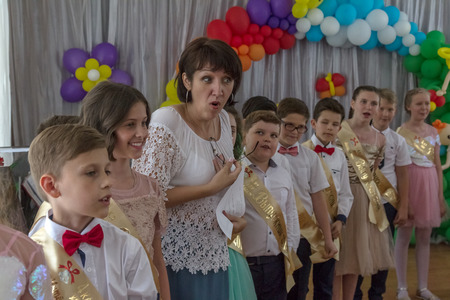 Odessa, Ukraine - May 31,2018: Children's musical group sing and dance on stage during graduation concert of elementary school. Children play. Emotional children's show on stage. Children's creativity Standard-Bild - 127003537