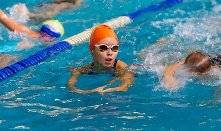 ODESSA, UKRAINE - CIRKA 2016: Children, athletes, swimmers swim along tracks in sports pool for swimming. Sports swimming in pool. Summer Olympic sport, healthy lifestyle, childrens sport