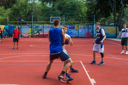 ODESSA, UKRAINE - JULY 28, 2018: Adolescents play basketball during 3x3 streetball championship. Young people play street basketball on an open city sports ground. Streetball - street cultures 에디토리얼