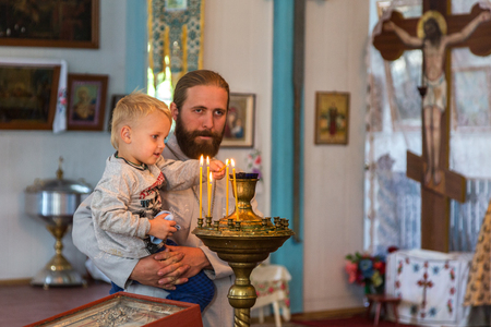 Ukraine, Odessa region, Kodyma, 2012 :, Interior of the Ukrainian Orthodox Church of the Moscow Patriarchate. The child lights a candle in the hands of the priest