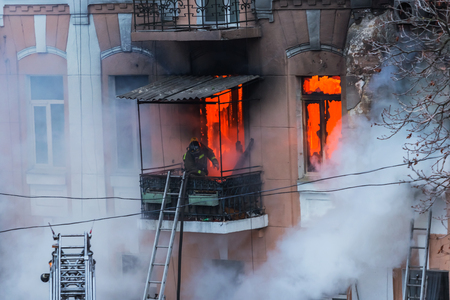 A fire in an apartment building. Strong bright light and clubs, smoke clouds window of their burning house. Firefighters extinguish fire in house. Work on fire stairs