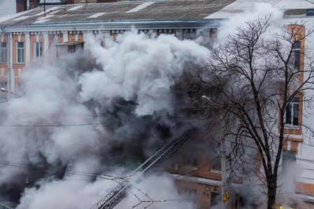 Odessa, Ukraine - Dec. 29, 2016: A fire in an apartment building. Strong bright light and clubs, smoke clouds window of their burning house. Firefighters extinguish fire in house. Work on fire stairs Editorial