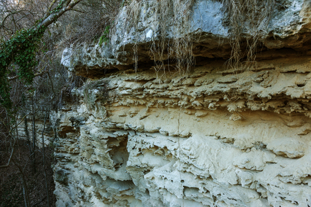 Picturesque background of collapsing surface of limestone rock. Abstract beautiful forms of weathering stone rocks, huge cracks and washed cavitie in stone, danger of collapse and landslide earthquake 版權商用圖片