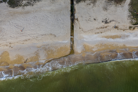 Discharge of dirty industrial wastewater in sea on city beach. Poisoning of recreation areas by spread of diseases, destruction of flora and fauna as result of violation of the ecology of sea coast