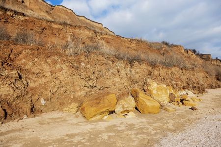 Landslide zone on Black Sea coast. Rock of sea rock shell. Zone of natural disasters during rainy season. Large masses of earth slip along slope of hill, destroy houses. Landslide - threat to life 스톡 콘텐츠