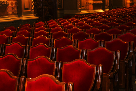 Interior theater art. Audience with empty soft armchairs of Opera and Ballet Theater is waiting for audience. Empty interior of concert theater before performance and without spectators. Soft focus