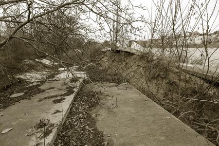 Landslide caused by rains of hurricane destroyed expensive cottages and houses. Destroyed house, cottage, large cracks, chips, slabs. Broken asphalt shifted landslide after earthquake. View from drone
