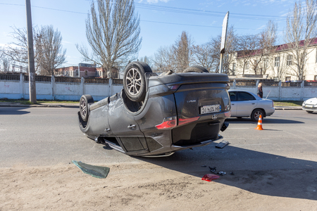 ODESSA, UKRAINE March 19, 2019: after car accident, broken car rolled over and lay down on roof on road that other cars drive. Concept of careless driving, breaking rules and speeding on road