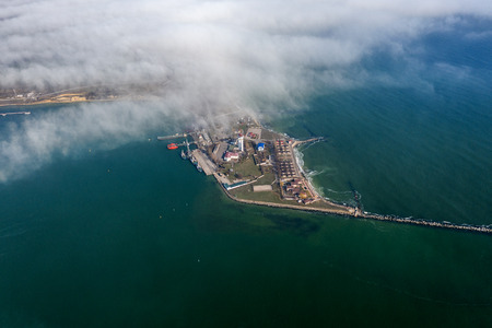 Aerial view of panoramic seaport warehouse and container ship, crane vessel working for delivery of delivery containers. Yuzhny Sea Industrial Port, Port Plant, Ukraine, 2019. Ships in sea port, fog