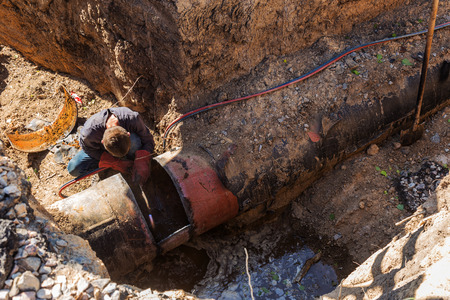 Replacement, dismantling of old worn water pipes. Welding work on cutting old rusty pipes. Replacement of old rusty metal water pipes. Welder cuts metal with gas torch