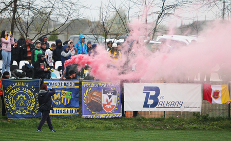 ODESSA, UKRAINE - April 13, 2019: large crowd of spectators in stands of stadium during match. Football fans hold fireworks with thick red sparkler smoke. Football fans lit rockets and smoke bombs