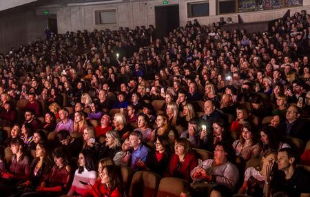 Odessa, Ucrania - 12 de abril de 2019: Multitud de espectadores en el concierto de rock ALEKSEEV durante el espectáculo musical. Multitudes de personas felices disfrutan del concierto de rock, levantan la mano y aplauden, audiencia en el podio Editorial