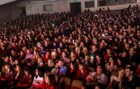 Odessa, Ukraine - April 12, 2019: Crowd of spectators at rock concert ALEKSEEV during music show. Crowds of happy people enjoy rock concert, raise their hands and clap their hands, audience on podium