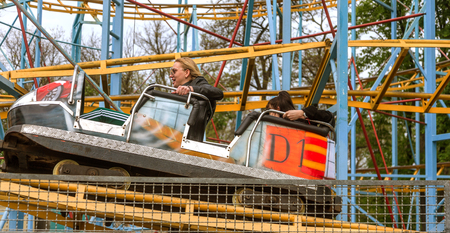 ODESSA, UKRAINE - MAY 6, 2019: Visitors ride road slides in an amusement park. Young friends on an exciting rollercoaster. Young people having fun in an amusement park. Scary fun on roller coaster
